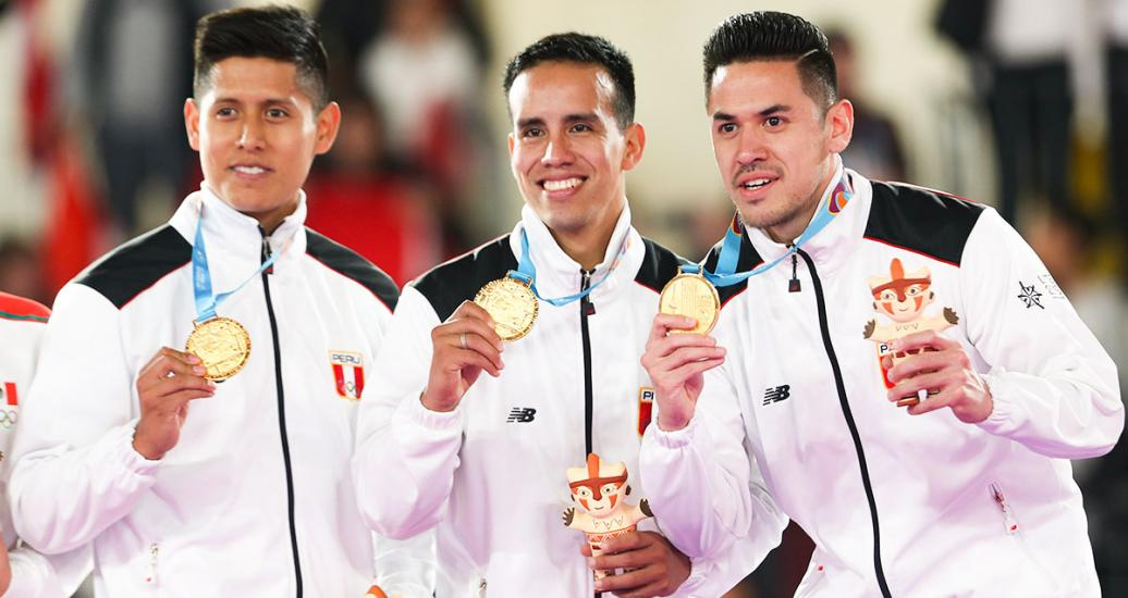 Peruvians Jhon Trebejo, Oliver del Castillo, and Carlos Lam celebrate the gold achieved in Lima 2019 team karate kata event after beating their Mexican counterparts at the Villa El Salvador Sports Center