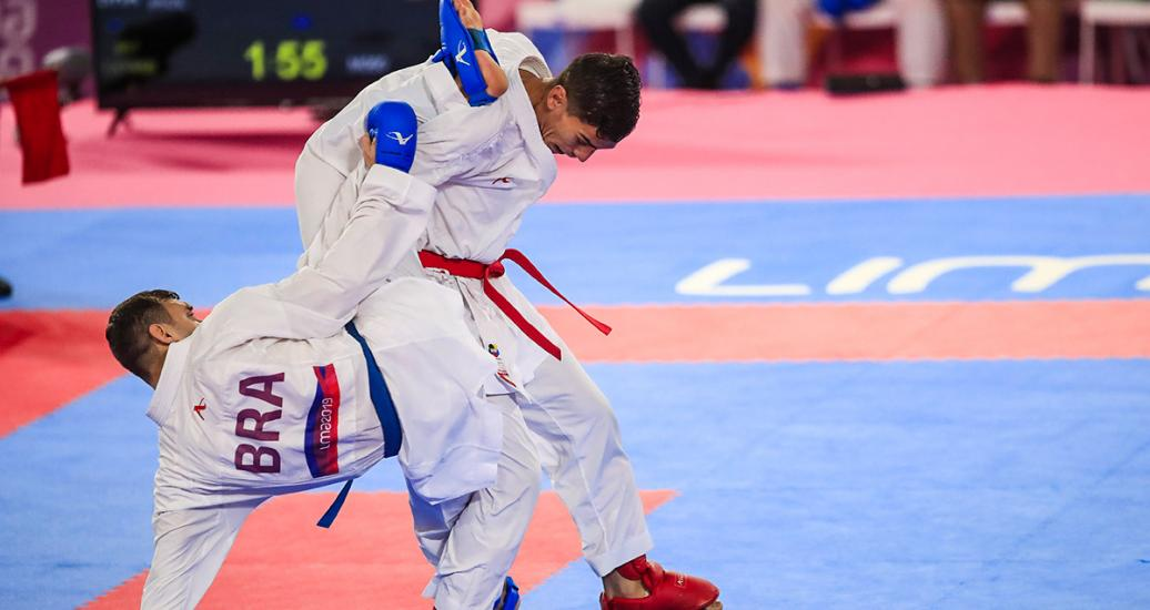 Jovanny Martinez from the Dominican Republic performs a move on Douglas Brose from Brazil in the Lima 2019 Pan American Games karate competition, at the Villa El Salvador Sports Center.