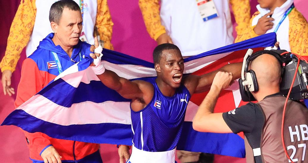 Cuban David Caballero celebrates holding his country's flag after winning in the men's flyweight category at the Callao Regional Sports Village
