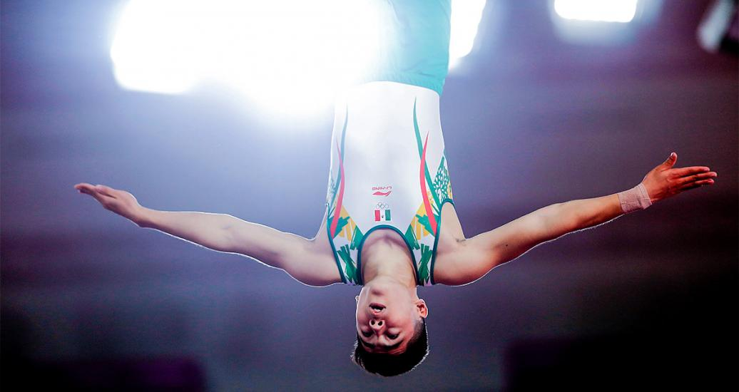 Mexico's Víctor Rodríguez soars through the air upside down and with arms extended in the trampoline competition of the Lima 2019 Games at the Villa El Salvador Sports Center