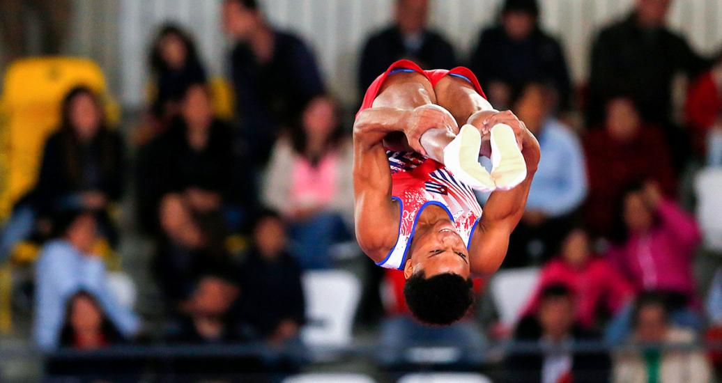 Cuba's Alexander Rodríguez jumps with legs extended in the trampoline competition at the Lima 2019 Games held at the Villa El Salvador Sports Center