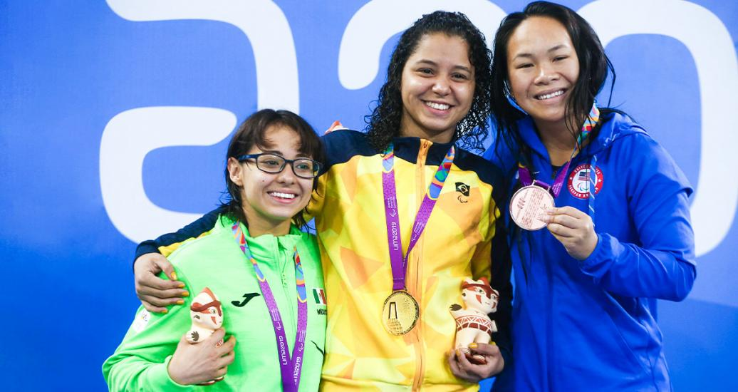 Paola Ruvalcaba from Mexico (silver), Cecilia Araujo from Brazil (gold) and Haven Shepherd from the USA (bronze) proudly smile on the women's 50m freestyle S8 Para swimming podium at Lima 2019 at the National Sports Village – VIDENA.