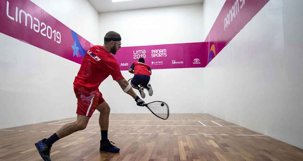 American racquetball player Jacob Bredenbeck hits the ball during the men's round of 16 against Ramón de León from the Dominican Republic at the Callao Regional Sports Village