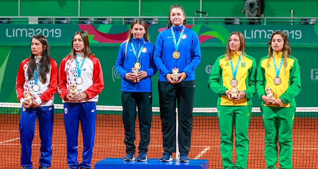 Women's doubles tennis players from Brazil (bronze), Paraguay (silver) and the USA (gold) posing with their medals at the Lawn Tennis Club.